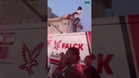 Large crowds party on top of and around ambulance after