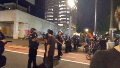 Portland Police watch Antifa protesters surround and harass a live-streamer.